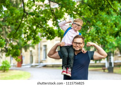 Father and kid have fun - child on dad's shoulders. Parent taking child to school. Back to school. Superman dad and son having fun. Concept of friendly family.