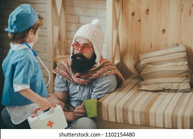 Father and kid playing clinic. Man in knitted white hat and colorful scarf sitting on floor with hot medicine. Bearded man in toy red glasses drinking tea. Boy dressed as doctor playing with dad.