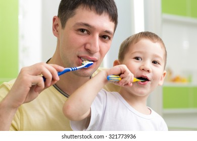 father and kid son brushing teeth together in bathroom