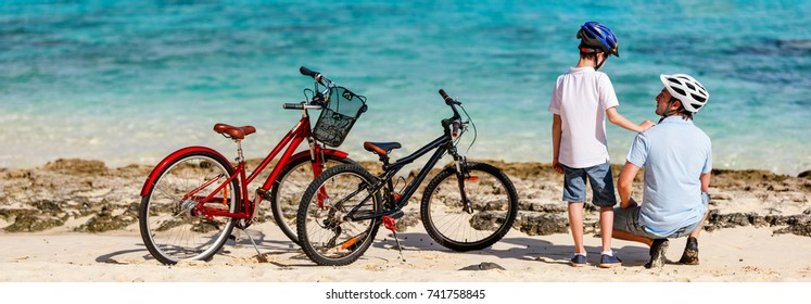 Father and kids enjoying sea view at tropical beach with their bikes parked nearby