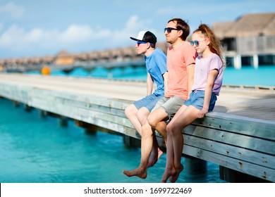 Vater und Kinder, die den Sommerurlaub am Strand im tropischen Inselresort genießen