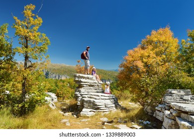 Father and kids exploring Stone forest, natural rock formation, created by multiple layers of stone, located near Monodendri village in Zagori region, Epirus, Northern Greece.