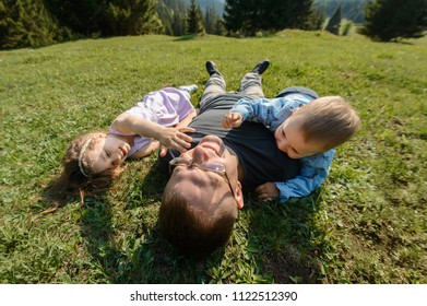 father and kids laying on grass and making fun