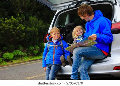 father with kids looking at map while travel by car