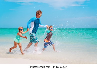 father with kids play with water run on beach