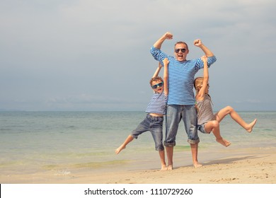 Father and kids playing on the beach at the day time. They are dressed in sailor's vests. Concept of sailors on vacation and friendly family.