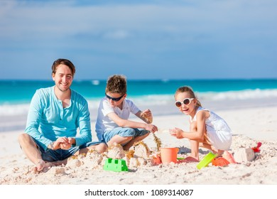Father and kids playing with sand on beach while enjoying summer vacation