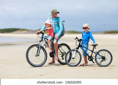 Father and kids riding bikes along a beach