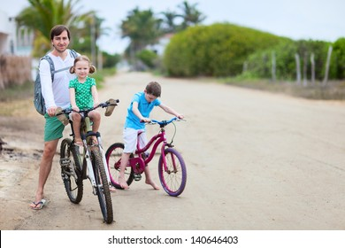 Father and kids riding bikes on sandy road