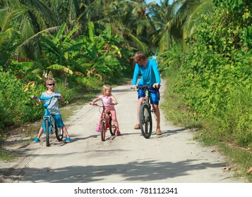 father with kids riding bikes on tropical vacation