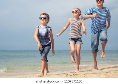 Father and kids running on the beach at the day time. They are dressed in sailor's vests. Concept of sailors on vacation and friendly family.