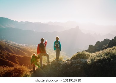 Father with kids travel in sunset mountains, family hiking in nature