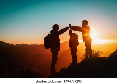 father with kids travel in sunset mountains, family high five in nature