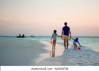 Father and kids walking on white sandy beach