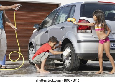 Father and kids washing the car at home.