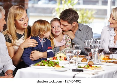 Father kissing daughter in restaurant while eating out with the family