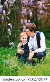 Father is kissing his baby boy on top of the head with a wysteria blooming in the background