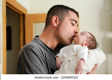 Father kissing his newborn baby girl. Close-up portrait