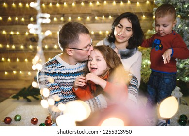 father kissing smiling daughter in christmas