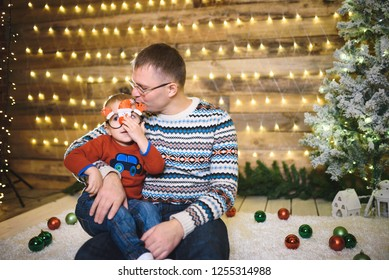 father kissing son that holding christmas glasses
