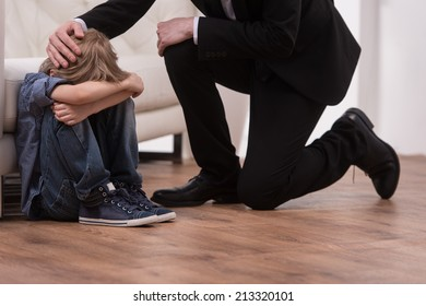 Father kneeling and comforts sad child. boy sitting on floor in bedroom and crying