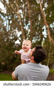 A father laughs and interacts with his baby girl outside.