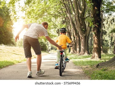 Father learn his little son to ride a bicycle