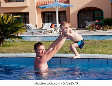 father learning his son to dive into the pool