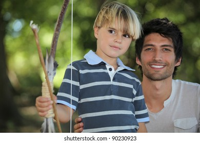 father learning his son how to draw a bow