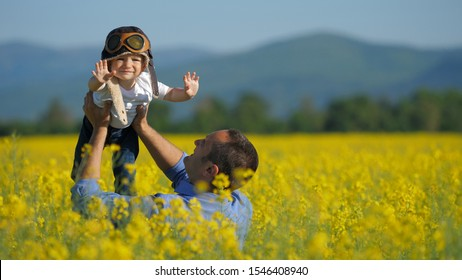 Father lifting up baby over blossom rape field, cute child with pilot helmet flying, parent raising up child