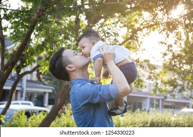Father lifting son in hand and pretending to wheel with pleasure on blur background at garden, Lifestyle and Family Concepts