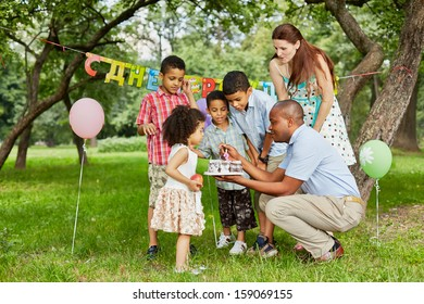Father lights candle on birthday cake with lighter, family of five looks at it, happy birthday sign behind their backs