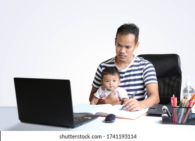 Father with little baby on knees making notes in notebook, looking at laptop. Young man holding child and working on PC. Parent sitting home and getting distant education. Dad doing homebased business