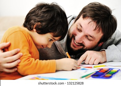 Father and little boy of fivr years having fun painting at home