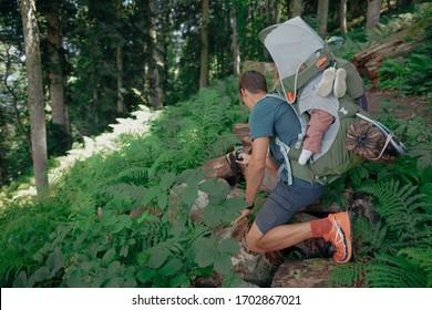 Padre y niño pequeño en el portador infantil a su espalda caminando en el bosque verde del verano en los días soleados, haciendo una foto en su smartphone