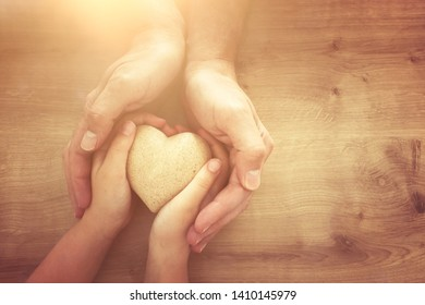 father and little child holding together wooden heart. Happy father's day concept.