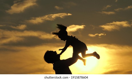 Father and little child play, laugh and hug together. Dad throws up a happy daughter in blue sky. Happy family travels. Baby in arms of the parent. Dad day off. Concept of a happy family. Silhouette