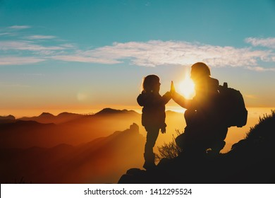 father and little daughter enjoy travel in mountains at sunset