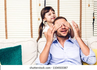 Father with little daughter having fun and playing close eye daddy on the sofa at home.little girl  surprise her daddy.Love of family and father day concept