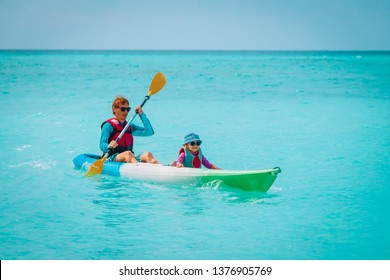 father and little daughter kayaking on beach