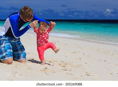 father and little daughter learning to walk on sand beach