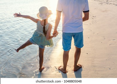 Father and little daughter on beach at sunset