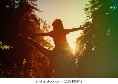 Father and little daughter silhouettes play at sunset