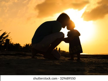 Father and little daughter silhouettes at sunset, parenting