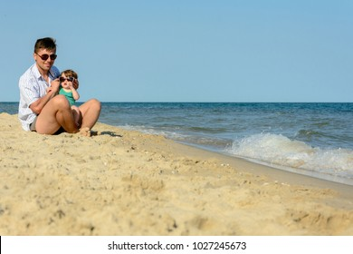 A father with a little daughter sits on the beach at the background of the sea