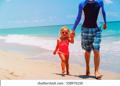 father with little daughter walk at beach