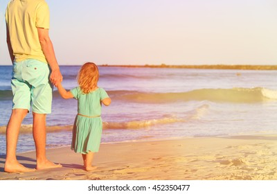 Father and little daughter walk on beach