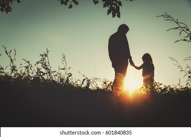 father with little daughter walk in sunset