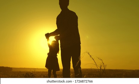father and little daughter whirl in dance at sunset. concept of happy childhood. Dad is dancing with child in her arms. happy child plays with his father at sunset. concept of happy family