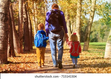 father with little son and daughter going to school